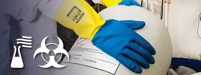 Trabalhador com luvas resistentes a produtos químicos Portwest manuseando itens perigosos.